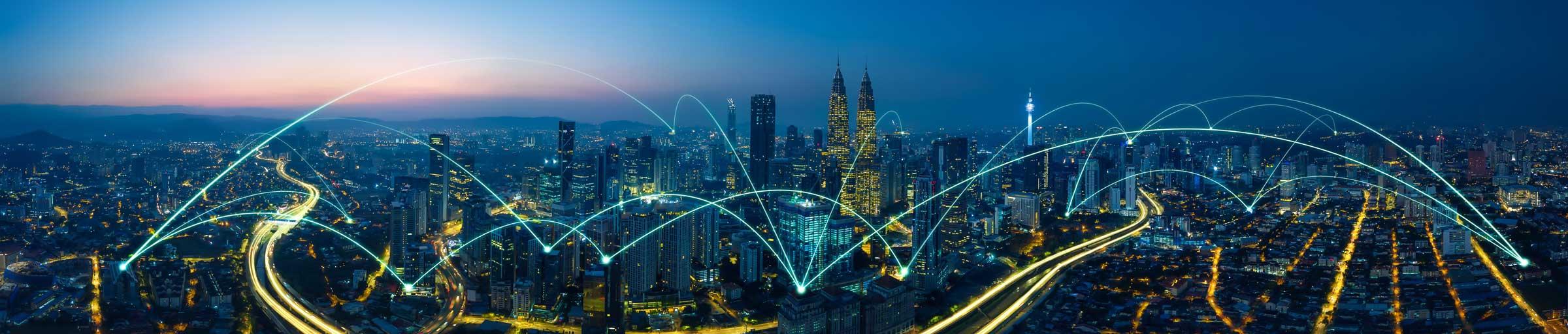Hier ist eine Skyline einer Großstadt im Abendrot zu sehen. Lichter brennen in den Häusern und Bürogebäuden. Durch Kameraeinstellungen werden diese Lichter auf den Straßen zu einer Linie zusammengeführt. Das Bild steht für Agilität und Technologie.