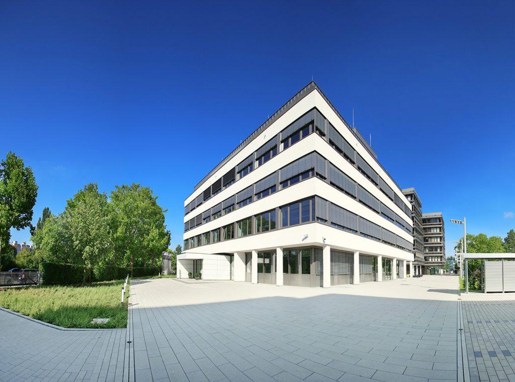 Hier ist der Eingang unserer Firmenzentrale in Nürnberg zu sehen. Das Gebäude ist erst ein paar Jahre alt und verfügt über vier Stockwerke. Die Außenfarbe ist weiß mit großzügigen Fenstern in alle Richtungen.