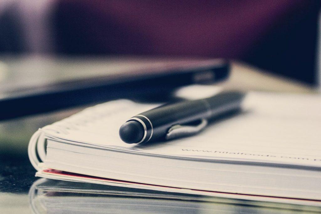 Auf diesem Bild liegt ein schwarzer Stift auf einem Notizbuch, dahinter leicht verschwommen ein Mobiltelefon. Der Tisch besteht aus einer Glasplatte.