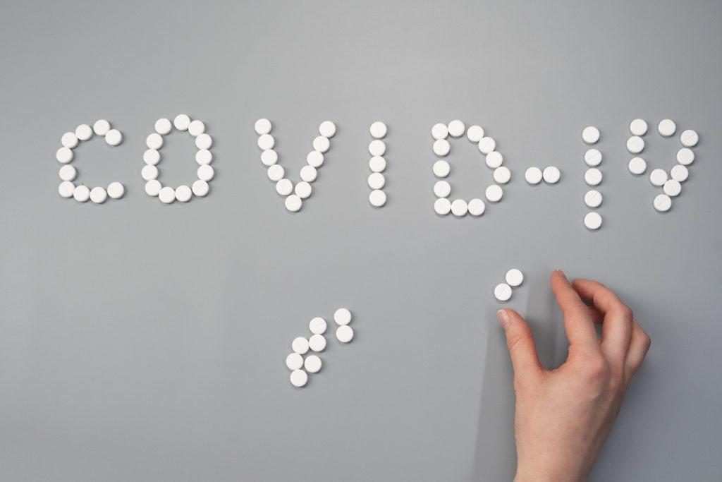 Ein Themenbild zur Corona-Pandemie, indem das Wort COVID-19 mit Pillen gesetzt wurde.